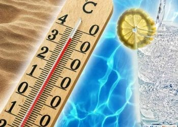 Conceptual image of hot summer days in the tropics with beach sand, a thermometer showing thirty degree temperatures and cool inviting blue water alongside a refreshing iced beverage