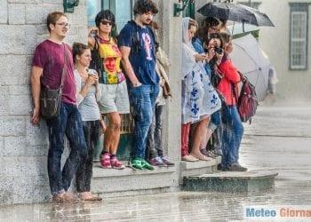 Gruppo di persone in attesa che cessi il forte acquazzone di un temporale estivo. Foto credit iStock