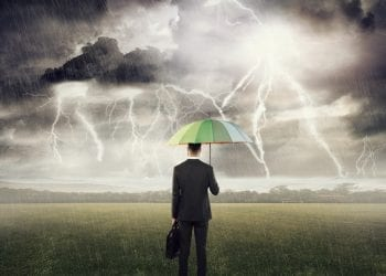 Rear view of a businessman standing with umbrella protecting himself from the storm concept for protection from recession or economic depression