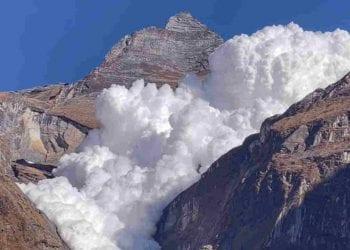 La valanga che scivola dalla montagna sopra il lago